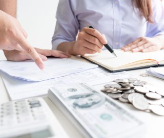couple working saving account book and calculating her monthly expenses on calculator to calculate financial data, filling in individual income tax return